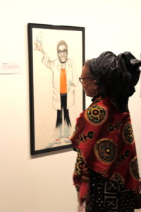 "Dr. M. Iyailu Moses enjoys a caricature of Dr. Witherspoon in the ""Lion's Tale"" Exhibit. - Jasmine Jack"