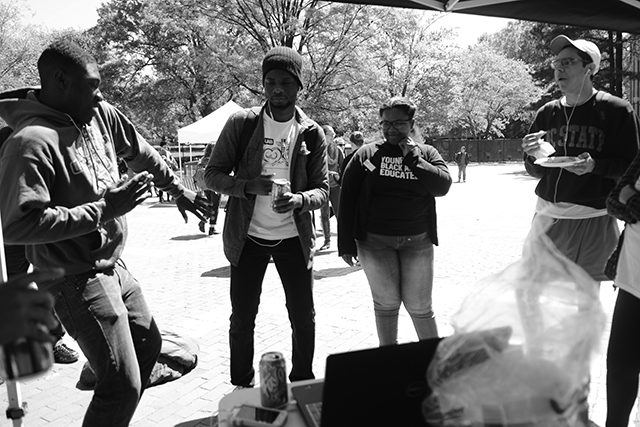 "Trevor Jenkins, a sophomore studying finance, busts a move while Ade Adesina, a sophomore studying communications, Tsharre Sanders, a senior studying psychology and Yerson Padilla, a senior studying women and gender studies look on during the Pan Afrikan Pride event held on the Brickyard Wednesday.  The event was held to promote Pan Afrikan Week through giving out free pizza, soda and chips as well as free T-shirts.  Sanders said that the purpose of the event was to ""bring people together."""