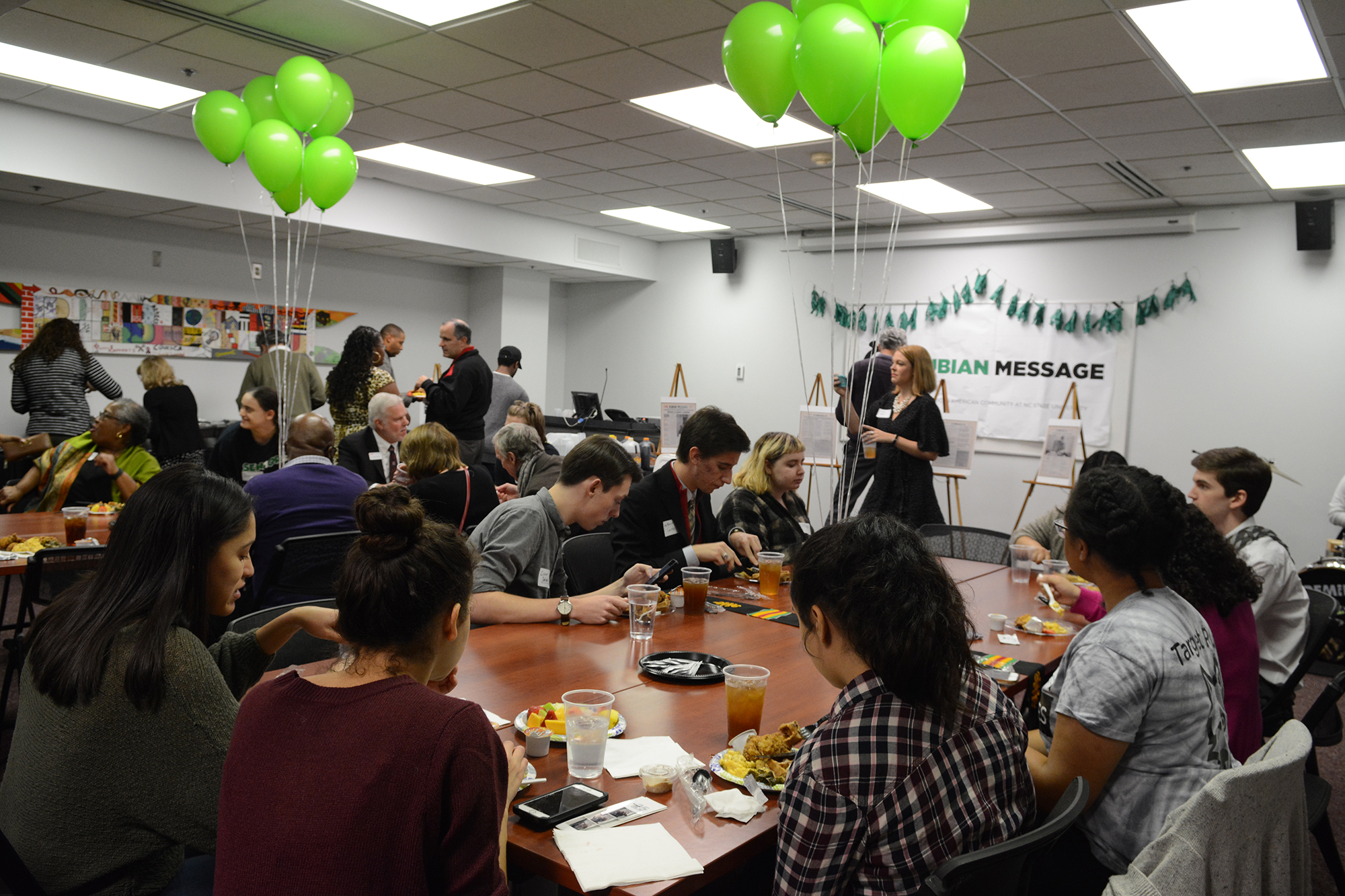 People eating at tables with green balloons. Large Nubian Message poster on wall in background.