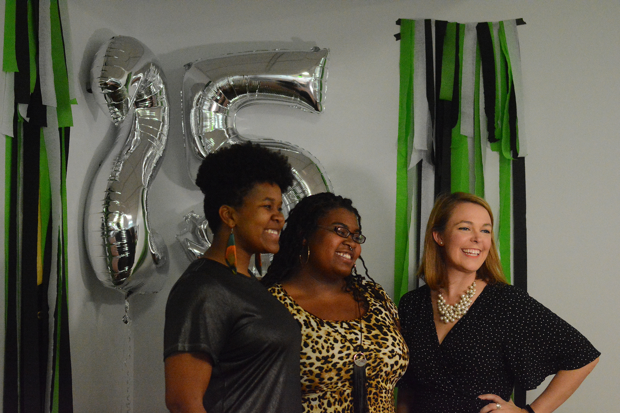 Three women pose in front of silver balloons and green streamers at photo booth