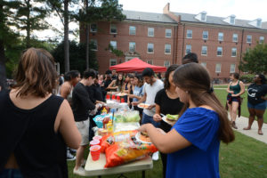 Students wait in line, outside of Alexander and Turlington residents hall, for carne asada and hamburgers at the LatinX Cookout on Friday, Sept. 15, 2015.