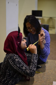 Vice President of the Muslim Student Association, Sinthia Shabnam gives classmate Soho Raja a henna tattoo at the Islam Fair on Tuesday Oct 24, 2017.