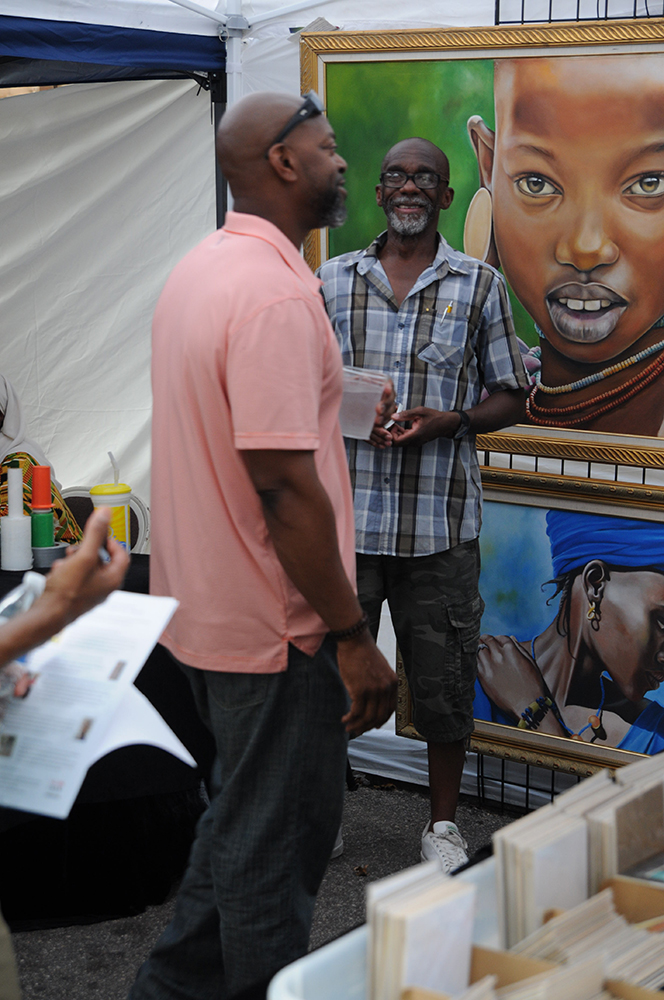 Abdul Badi interacts with a festival goer who stopped to look at his paintings during the African American Cultural Festival of Raleigh and Wake County on Saturday, Sept. 1, 2018. Badi is an artist native to New York who specializes in oil and pastel media with strong traditional African influences to his work. (Glenn Wagstaff/Staff Photographer)