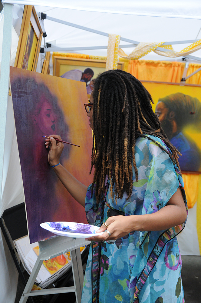 Dare Coulter paints at her vendor booth at the African American Cultural Festival of Raleigh and Wake County on Saturday, Sept. 1, 2018. Coulter is an NC State graduate of the class of 2015 and works in ceramic sculptures, paintings, murals, and drawings. She hopes to have painted a mural on every continent within the next two years. (Glenn Wagstaff/Staff Photographer)