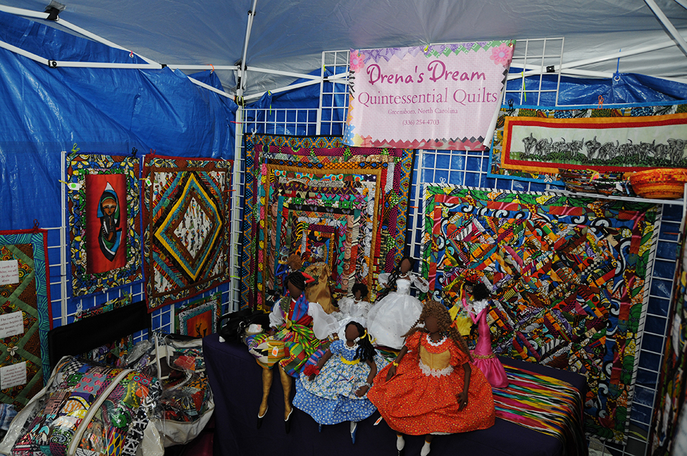Vibrantly colored quilts and dolls hang on display at the 'Drena's Dream' vendors tent at the African American Cultural Festival of Raleigh and Wake County on Saturday, Sept. 1, 2018. The festival celebrated African American music, art, and culture with many blocks of vendors and three stages set up along Fayetteville Street. At the festival, vendors sell anything from food to highly unique art. (Glenn Wagstaff/Staff Photographer)