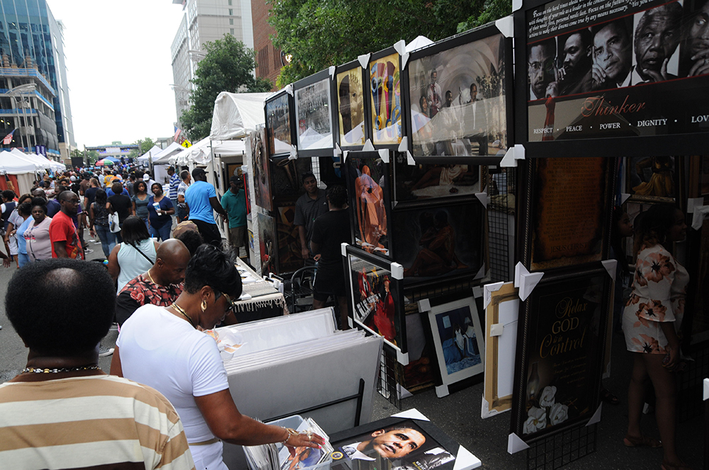 Festival goers peruse art and other wares at the African American Cultural Festival of Raleigh and Wake County in Downtown Raleigh on Saturday, Sept. 1, 2018. The cultural festival is an annual event that takes place on Labor Day weekend and celebrates African American cultures through art, music, storytelling, and other festivities. (Glenn Wagstaff/Staff Photographer)