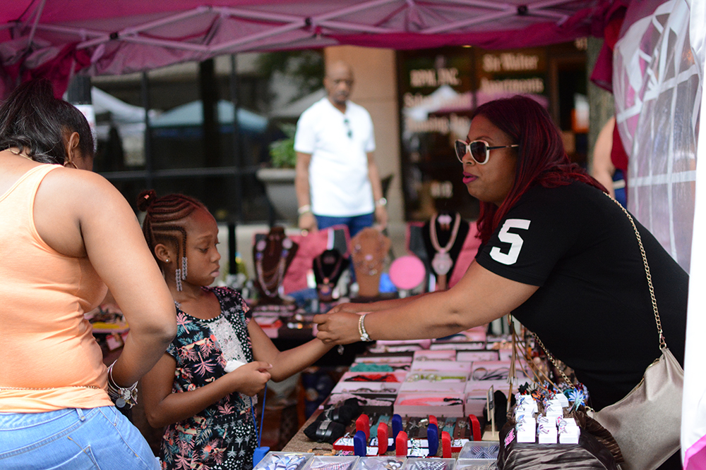 Visitor buys her kid cosmetics during the African American Culture Festival of Raleigh and Wake County on Saturday, Sept. 1, 2018. (Shanmukha Sandesh/Staff Photographer)