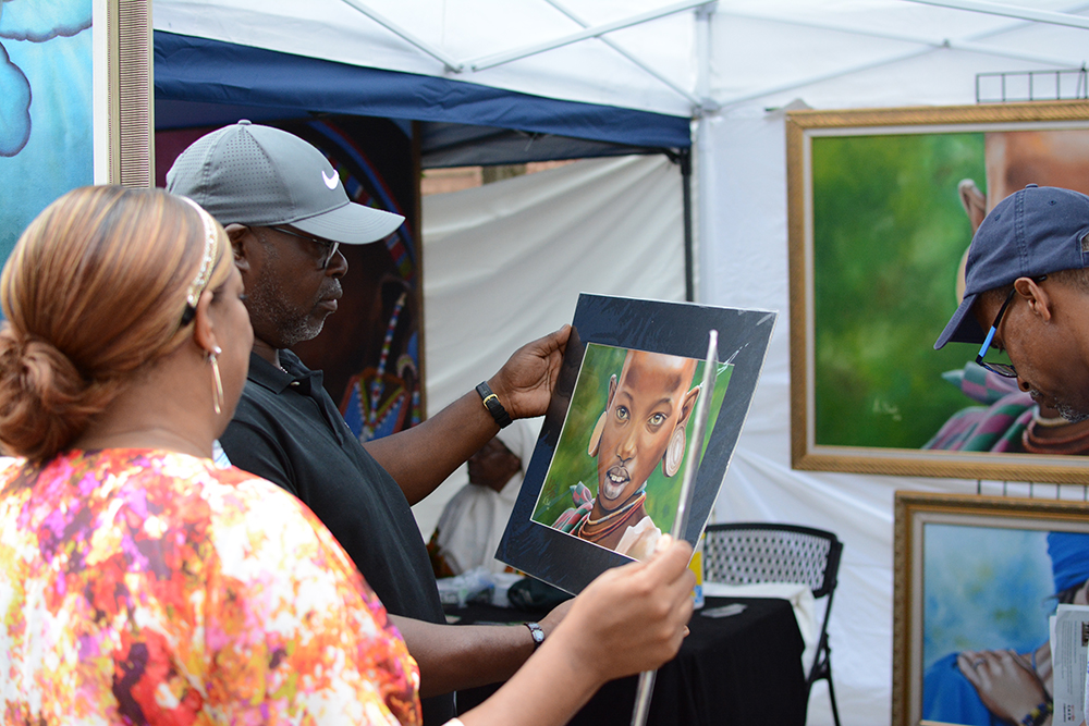 Visitors check out the art work by Adbul Badi during the African American Culture Festival of Raleigh and Wake County on Saturday, Sept. 1, 2018. (Shanmukha Sandesh/Staff Photographer)