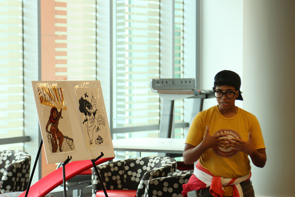 """Artist Q Wideman explains the emotions in their paintings at the exhibition """"My Art is Resistance"""" on October 9, 2018 in Talley Student Union. (Shanmukha Sandesh/Staff Photographer)"""