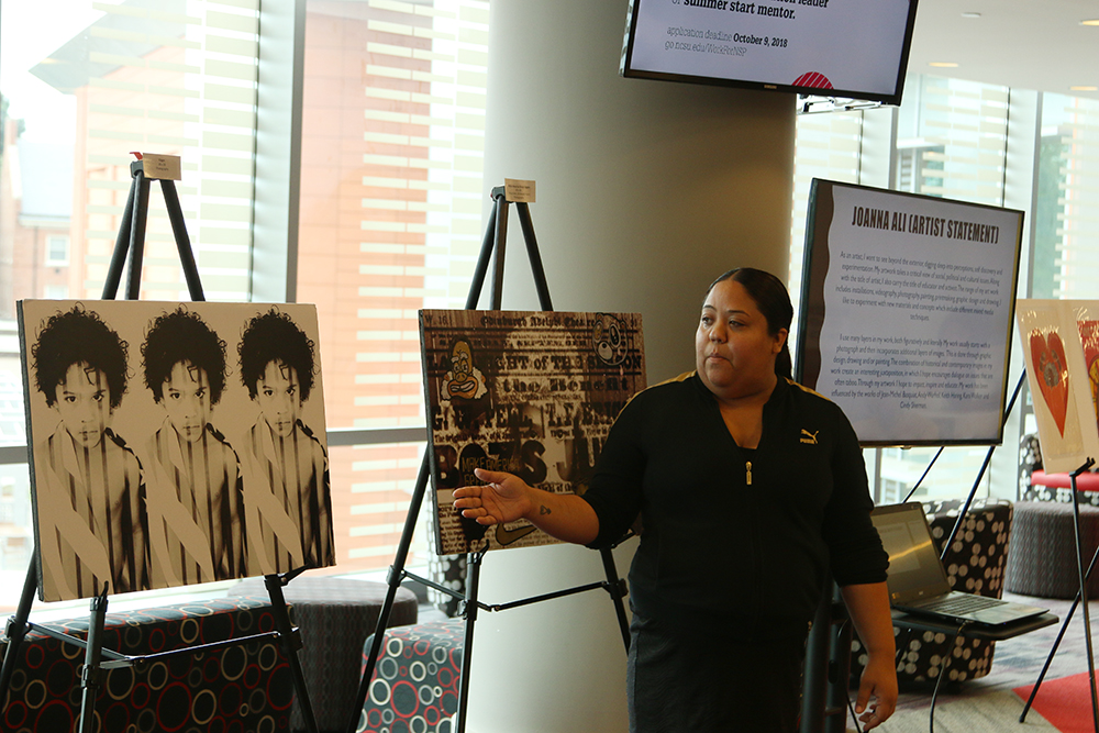 """Artist Joanna Ali explains the emotions in her art at exhibition """"My Art is Resistance"""" on October 9, 2018 in Talley Student Union. (Shanmukha Sandesh/Staff Photographer)"""