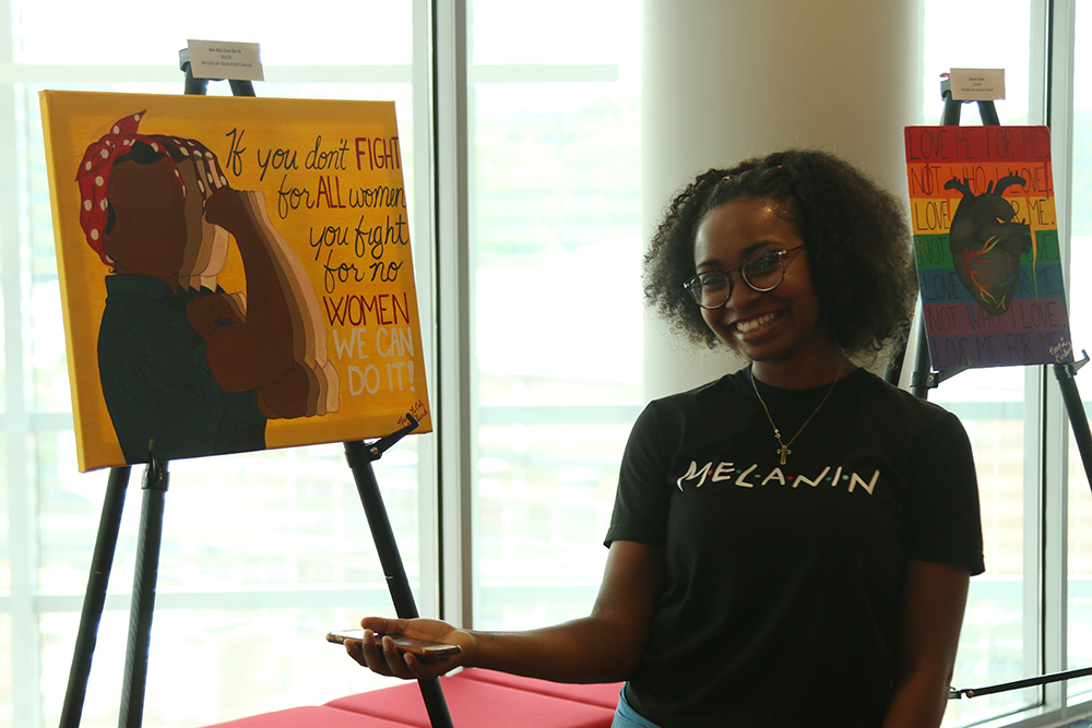 """Artist Nieya Garland with her paintings at the exhibition """"My Art is Resistance"""" on October 9, 2018 in Talley Student Union. (Shanmukha Sandesh/Staff Photographer)"""