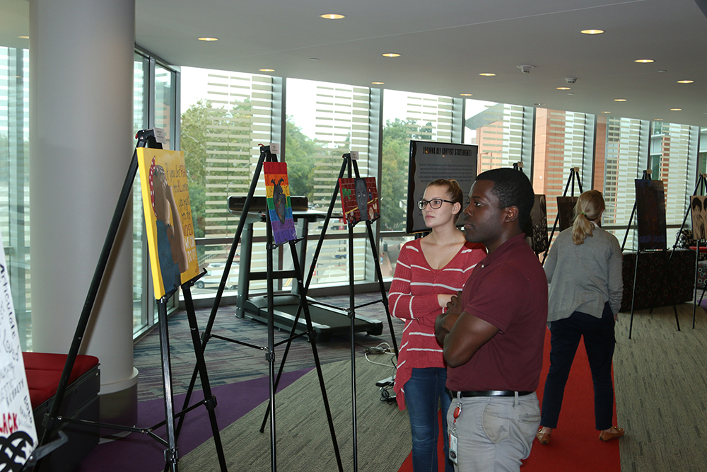 """Oppong Hemeng and Dana Petre were exploring the painitings at the exhibition """"My Art is Resistance, NM Gallery"""" on October 9, 2018 in Talley Student Union. (Shanmukha Sandesh/Staff Photographer)"""
