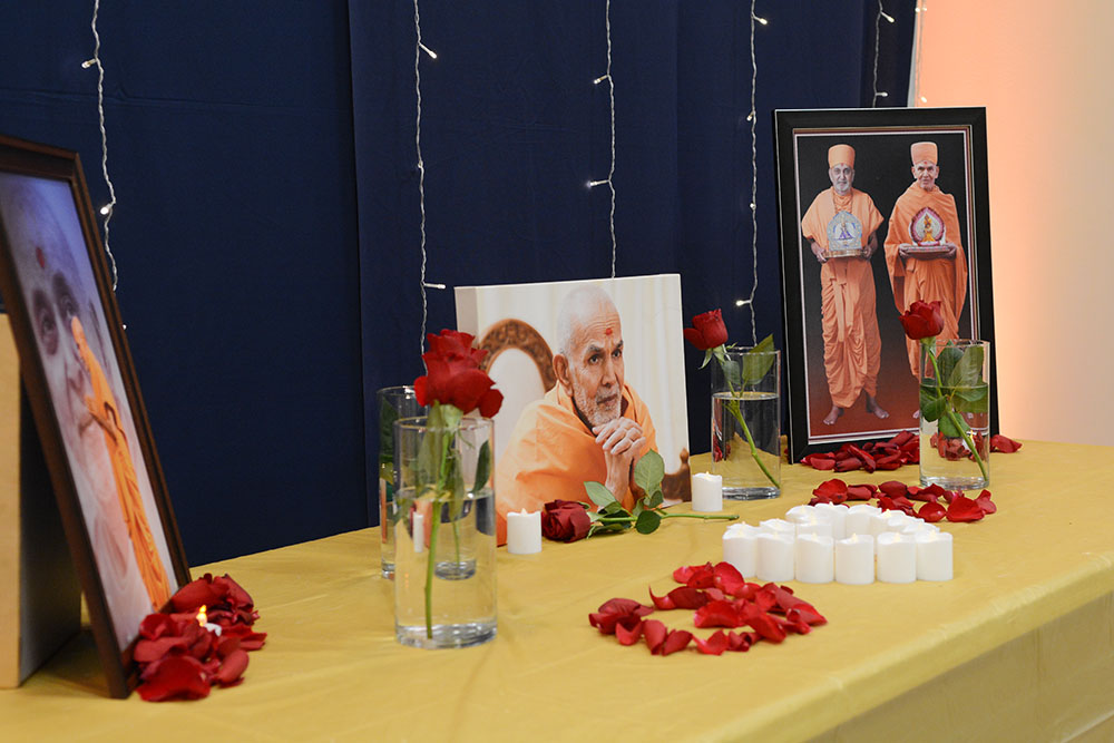 A display table with photographs of BAPS spiritual leaders sits in Riddick Hall during the BAPS Diwali celebration on Friday, November 2. 2018. BAPS is a branch of Hinduism and Diwali is a festival of lights, regarded as the Hindu new year. (Amrita Malur/Staff Photographer)