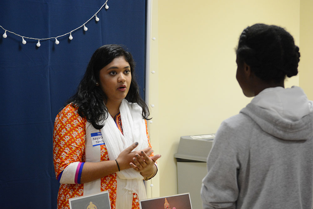 Aayushi Patel, a member of the BAPS mandir, explains the meaning of Diwali during the BAPS Diwali celebration in Riddick Hall on Friday, November 2, 2018. BAPS Campus Fellowships across North Carolina have been hosting the event at NC State for the past four years. BAPS is a branch of Hinduism and has a mandir, or temple, in Morrisville, North Carolina. (Amrita Malur/Staff Photographer)