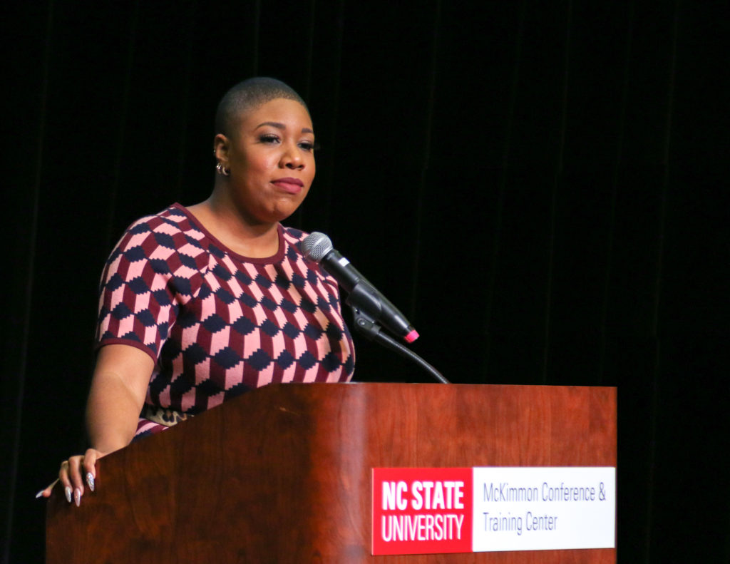 Symone Sanders stands at a podium in McKimmon Center to deliver the MLK Campus Commemoration speech.