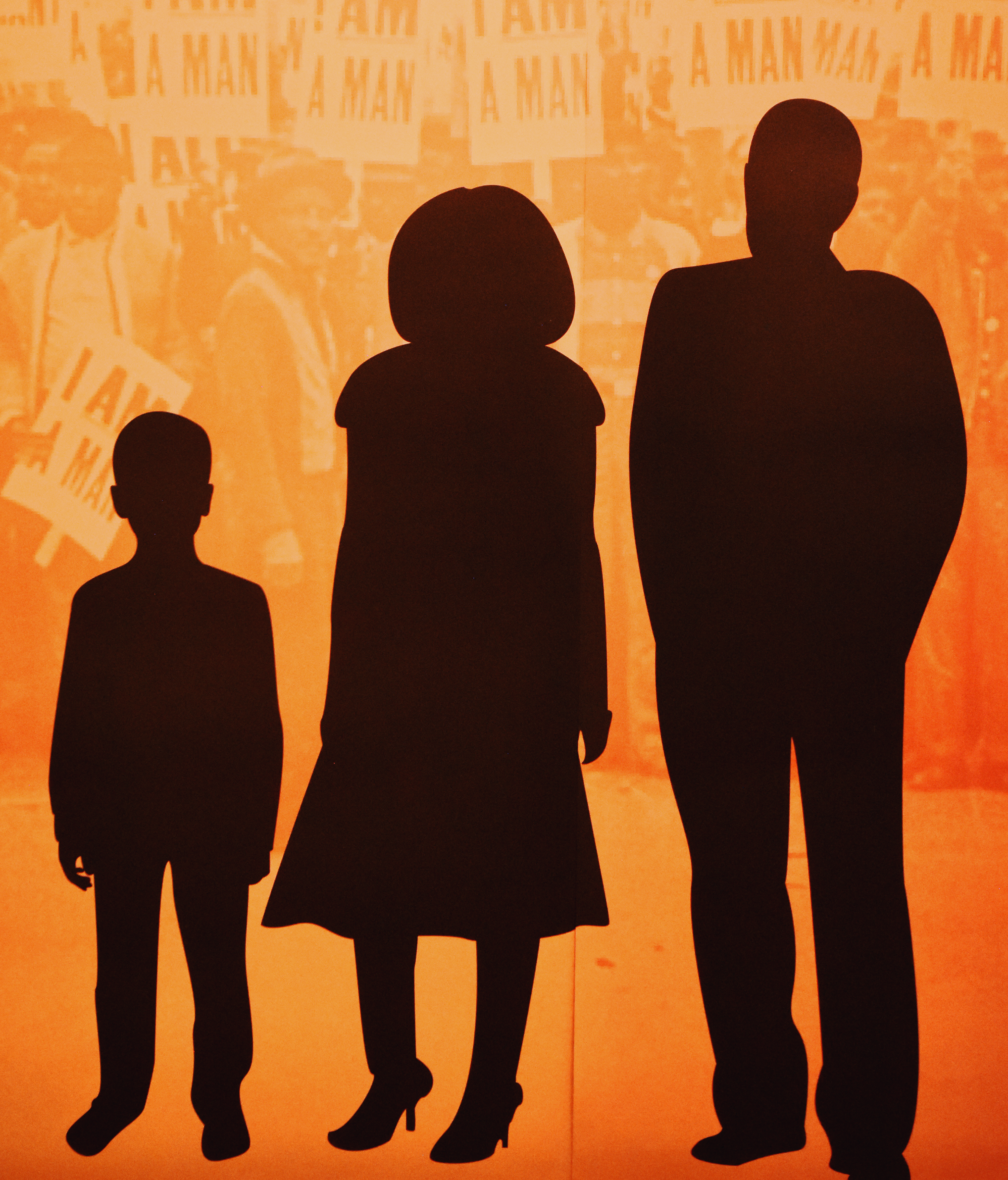 "The silhouettes of a family can be seen underneath the story of a sanitation worker at the ""I Am A Man"" exhibit."