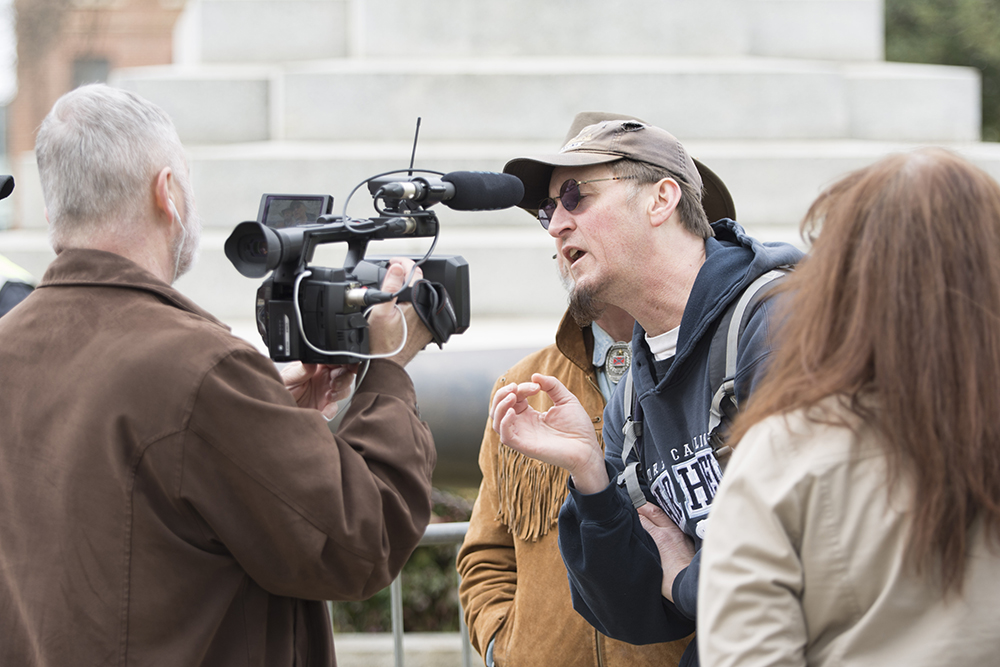 Michael, a anti-Confederate protester, interrupts an interview with a local news outlet and an Heirs to the Confederacy counter-protester. (Kaydee Gawlik/Nubian Message)