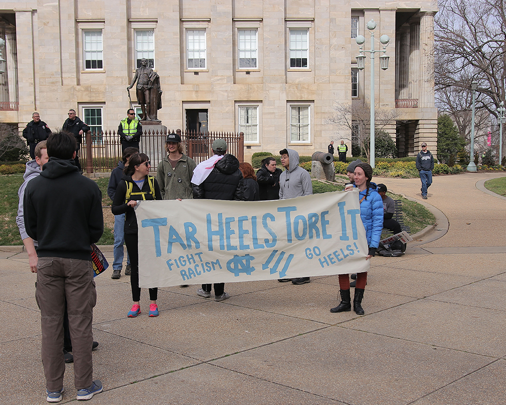 Protesters hold up a sign at the Crush Confederates at the Capital event on Saturday, Feb. 9 at the North Carolina State Capitol in Raleigh. The sign was up for a short time before on site officers requested its removal to comply with city ordinance laws. (Aditya Penumarti/Nubian Message)